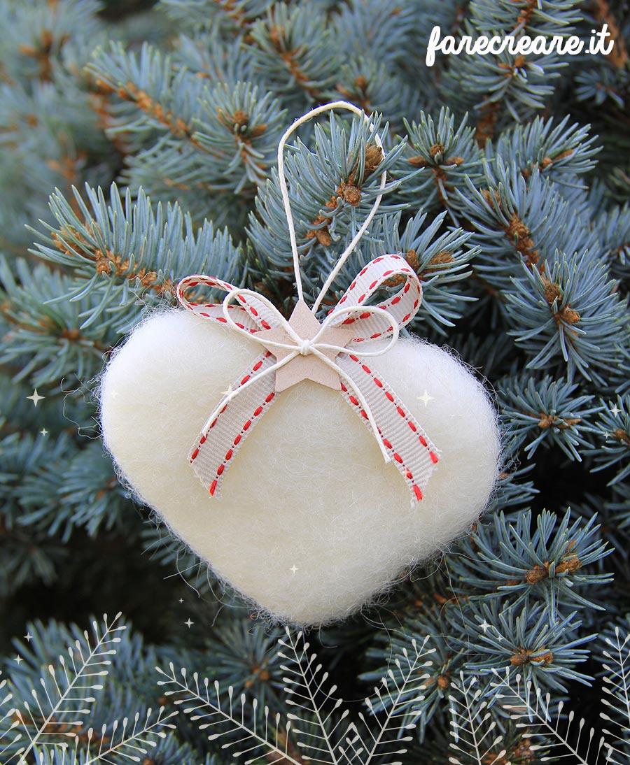 Cuore in lana cardata per Natale - colore bianco con pino argentato sullo sfondo.