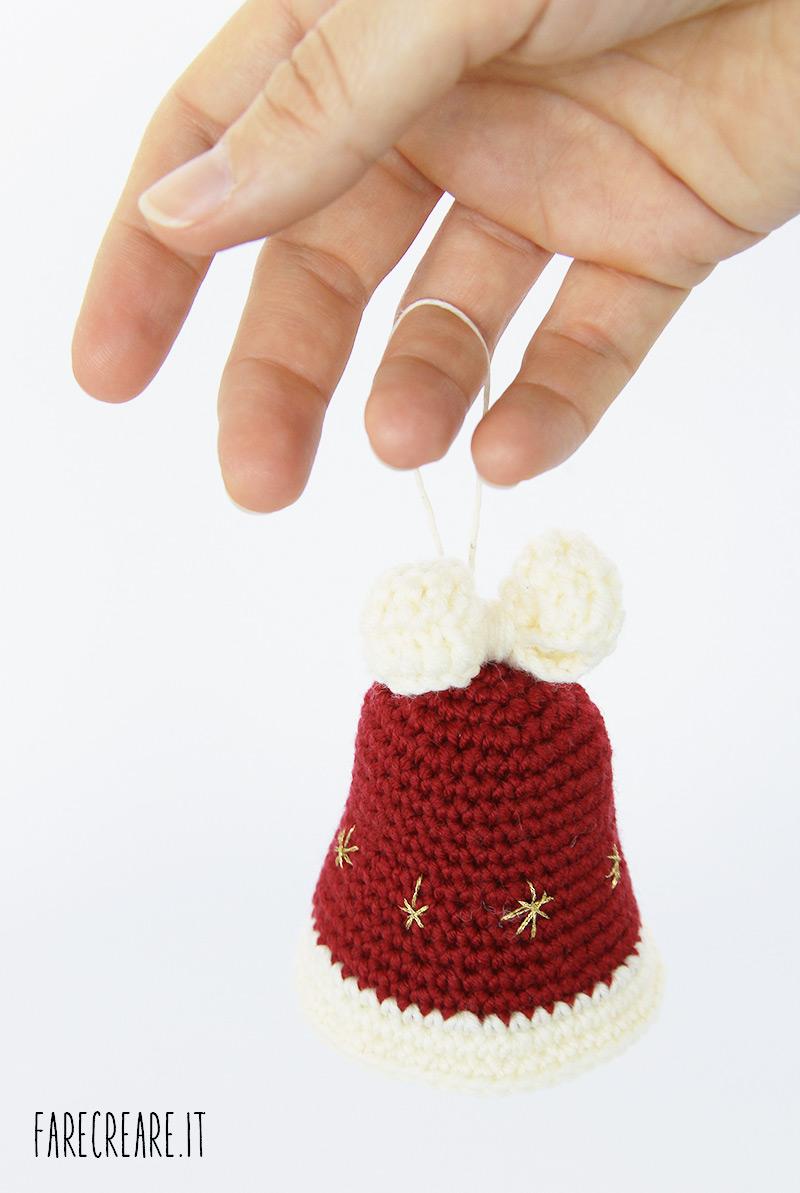 Campana di Natale rosso scuro con fiocco bianco.