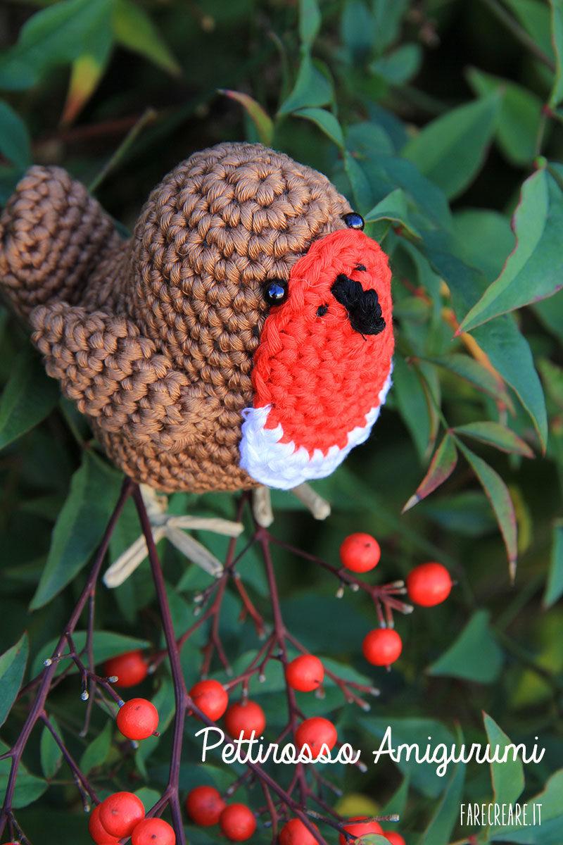 Pettirosso amigurumi lavorato a uncinetto appoggiato su pianta con bacche rosse.
